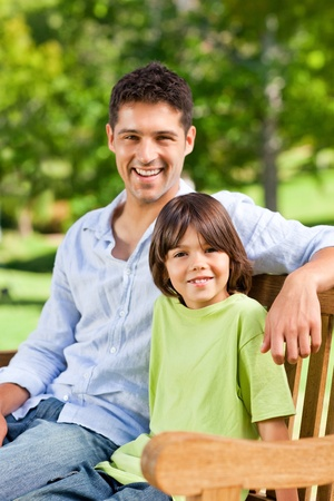 Son with his father on the bench photo