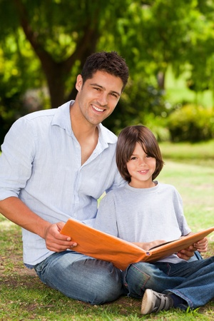 Son with his father looking at their album photo Stock Photo - 10192198