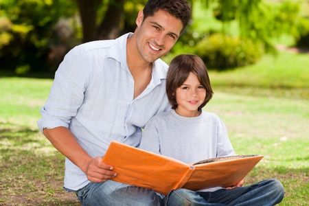 Son with his father looking at their album photo Stock Photo - 10192085