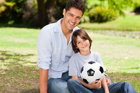 Father and his son with their ball in the park photo