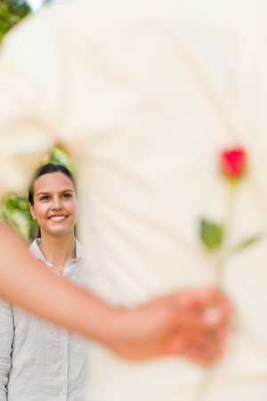 Happy man offering a rose to his girlfriend photo
