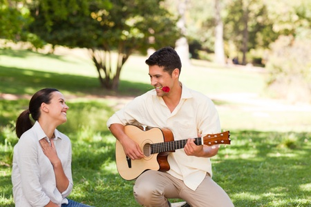 Man playing guitar for his girlfriend photo