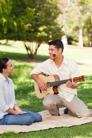 Man playing guitar for his girlfriend Stock Photo - 10190931