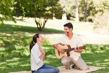Man playing guitar for his girlfriend Stock Photo - 10190940