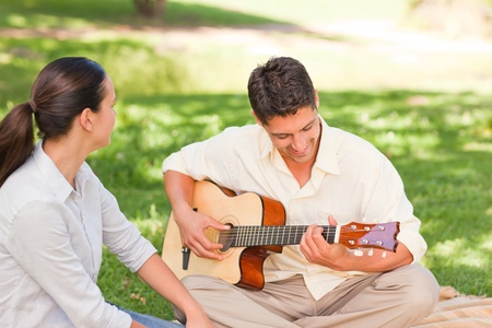 Romantic man playing guitar for his wife photo