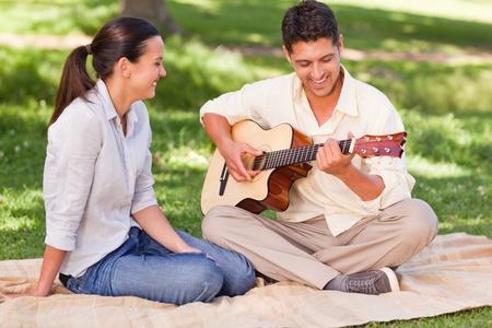 femme avec guitare: L'homme joue de la guitare romantique pour sa femme Banque d'images