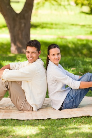 Couple sitting back to back in the park Stock Photo - 10190823