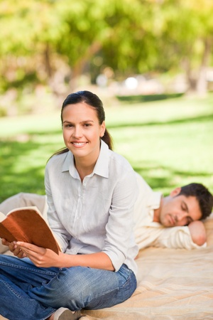 Woman reading while her husband is sleeping photo
