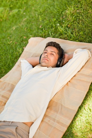 Young man listening to music in the park Stock Photo - 10192091