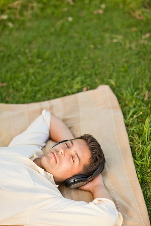 Young man listening to music in the park photo