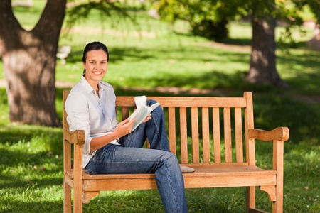 Young woman reading on the bench photo