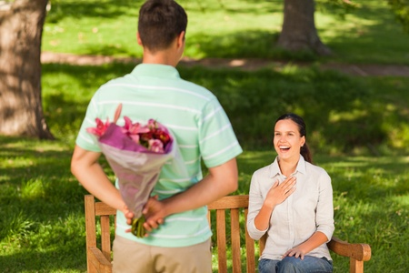 Young man offering flowers to his wife photo