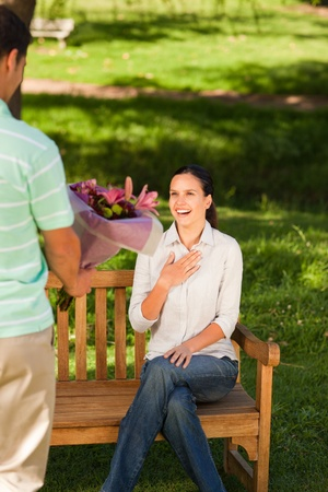 Young man offering flowers to his wife Stock Photo - 10190952