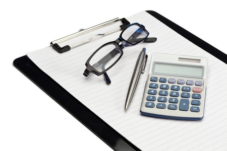 Angled note pad, pen, glasses and pocket calculator on a white background photo