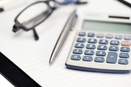 pad pen: Bloc de notas, bol�grafo, gafas y calculadora de bolsillo sobre un fondo blanco Foto de archivo
