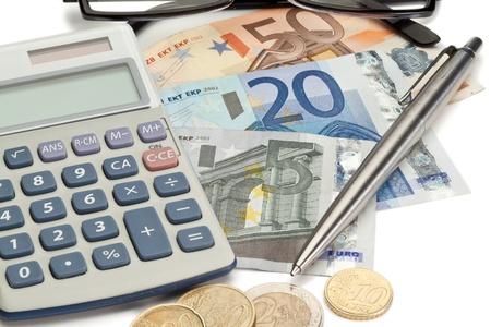 M�nzen und Bargeld mit Stift zusammen mit Brille und Taschenrechner auf wei�em Hintergrund