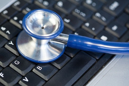 Blue angled stethoscope on keyboard on a blue background photo