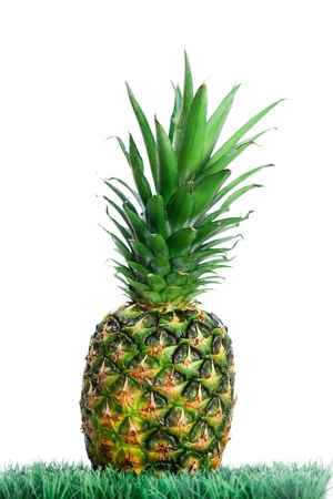 Pineapple on grass on a white background photo