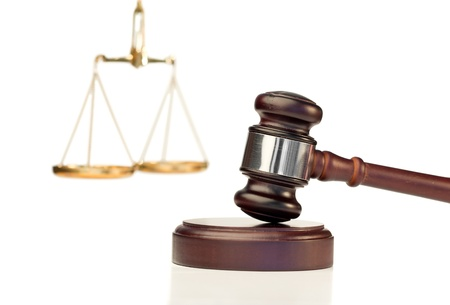 Gavel in action and scale of justice on a white background photo