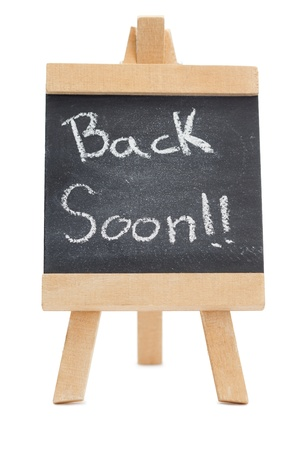 Chalkboard with the words back soon written on it isolated against a white background photo