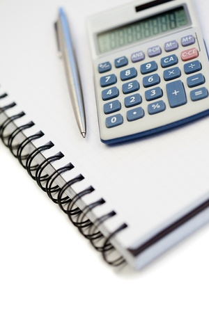 Angled notebook with pencil and pocket calculator on a white background photo