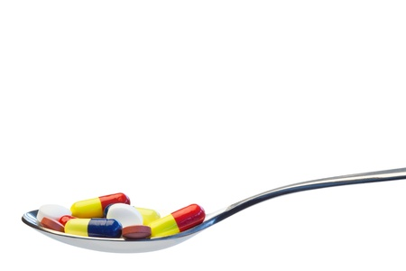 Spoon full of pills on a white background photo