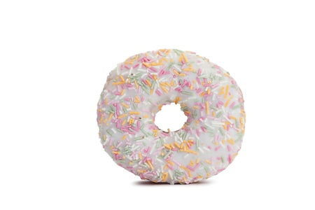 Pink Iced Doughnut covered in sprinkles isolated against white background photo