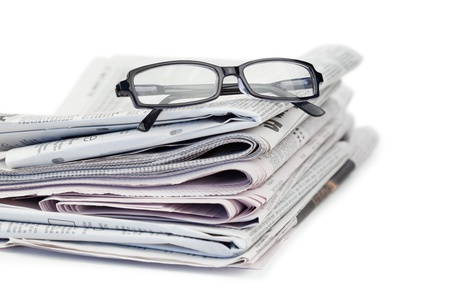 Newspapers and black glasses on a white a background photo