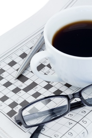 Newspapers and crossword puzzle on a white background photo
