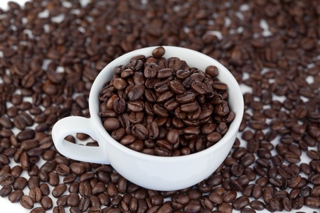 Small white cup of coffee with coffee beans on a grains background photo