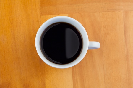 White cup of coffee isolated on a desk photo