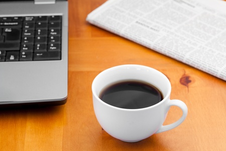 White cup of coffee with laptop and newspaper on a desk photo