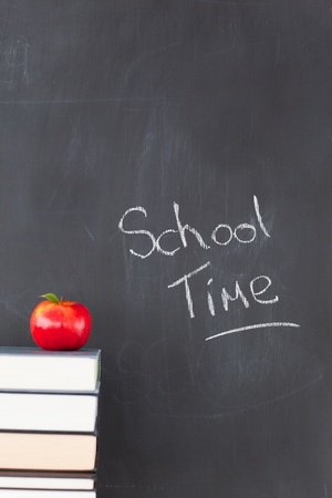 Stack of books with a red apple and a blackboard with school time written on it photo