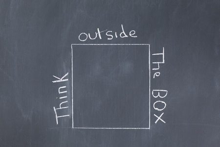 Words think outside the box written around a cube on a blackboard photo
