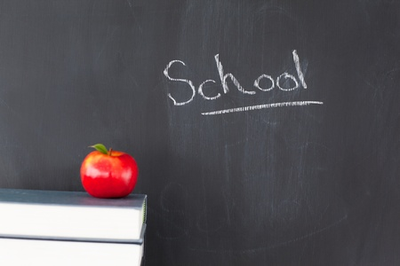 Stack of books with a red apple and a blackboard with school written on it photo