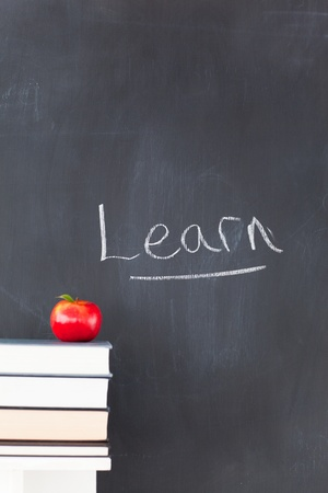 Stack of books with a red apple and a blackboard with learn written on it photo