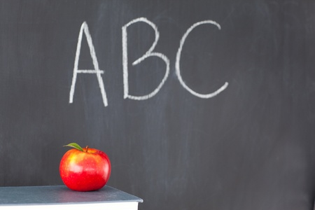 Stack of books with a red apple and a blackboard with ABC written on it photo