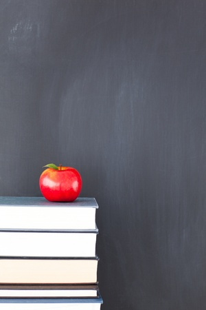 Stack of books with red apple and clean blackboard photo
