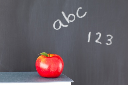 Stack of books with a red apple and a blackboard with figures and letters written on it photo