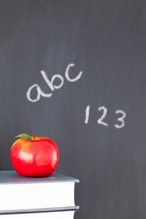 Stack of books with a red apple and a blackboard with figures and letters written on it Stock Photo - 10206658