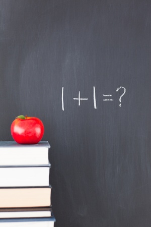 Stack of books with a red apple and a blackboard with 1+1=? written on it photo