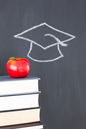 Stack of books with a red apple and a blackboard with a graduation cap drawn on it photo