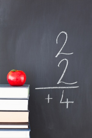 Stack of books with a red apple and a blackboard with a simple fraction written on it photo