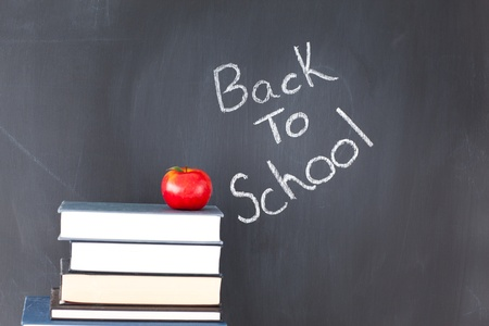 Stack of books with a red apple and a blackboard with back to school written on it photo