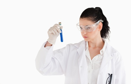 Dark-haired woman carrying out an experiment in a lab photo