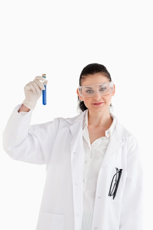 Dark-haired scientist looking at the camera while holding a test tube photo