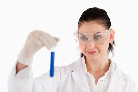 Isolated dark-haired scientist carrying out an experiment in a lab photo