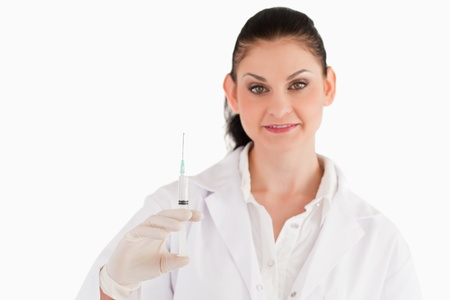 Doctor with syringe looking at the camera on a white background photo