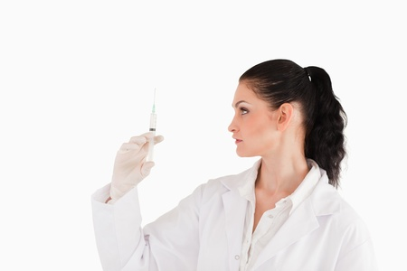 Doctor looking at a syringe on a white background photo