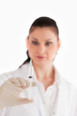 Doctor preparing a syringe on a white background photo